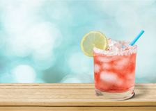 Delicious pink cocktail with ice and lemon on. Delicious pink ice cocktail lemon color background stock image