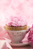 Delicious Pink Cupcake In A Teacup. A delicious pink cupcake in a china teacup, with feminine setup, pink background with selective focus, vertical with copy Stock Image