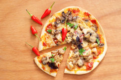 Delicious pizza. Tasty ready to eat crusty Italian pizza with tomato sauce, melting cheese, mushrooms, chicken, chili pepper, parsley and basil on texture wooden Stock Photo