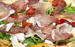 Delicious pizza with bacon, sausage, tomatoes and arugula Stock Photo