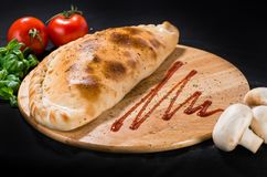 Delicious Pizza calzone with basil leaves on wooden board on dar. K background stock image