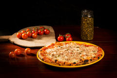 Delicious pizza with cheese, meat and sprouts on wooden table. Delicious pizza with mozzarella cheese and chicken and tomatoes on wooden paddle next to a bottle royalty free stock images