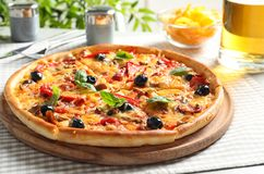 Delicious pizza with olives and sausages on table. Delicious pizza with cheese, olives and sausages on table royalty free stock photo