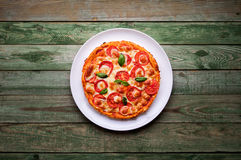 Delicious pizza with cheese on white plate. Pizza on wood table Stock Photo