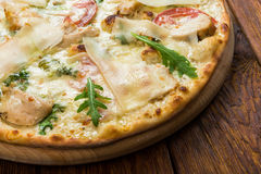 Delicious pizza with chicken, parmesan and fresh arugula Royalty Free Stock Photo