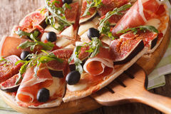 Delicious pizza with figs, ham, arugula and cheese macro horizon Royalty Free Stock Images