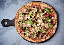 Delicious Pizza with Ham, Olives and Jalapenos. Delicious Freshly Baked Pizza with Ham, Black Olives, Jalapenos, Basil and Mozarella Cheese on Wooden Serving Stock Photo
