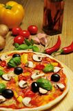 Delicious pizza and ingredients. Delicious pizza and some ingredients in the background stock photography
