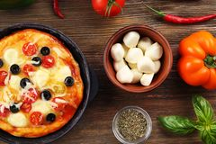 Delicious pizza with ingredients and spices Royalty Free Stock Photo