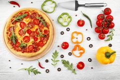 Delicious pizza with ingredients and spices Royalty Free Stock Images
