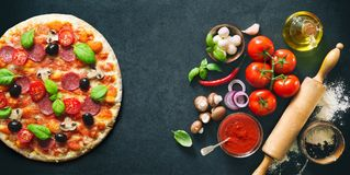 Delicious pizza with ingredients and spices Stock Photography