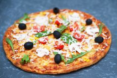 Delicious pizza and ingredients on stone background Stock Photo