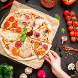 Delicious pizza with ingredients and woman hand on dark table. Flat lay. Top view. Italian food stock image