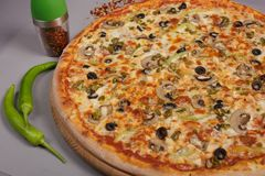 Delicious pizza Mexicana. Delicious pizza Mexicana with tomato sauce, mushrooms and chilli peppers with seasoning. Spicy food, made at home. Ingredients for royalty free stock photo
