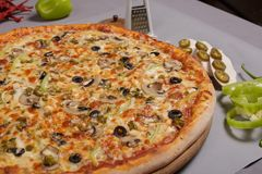 Delicious pizza Mexicana. Delicious pizza Mexicana with tomato sauce, mushrooms and chilli peppers with seasoning. Spicy food, made at home. Ingredients for stock image