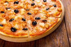 Delicious pizza with pineapple, chicken and olives Royalty Free Stock Images