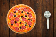 Delicious pizza with salam and mushrooms with steel cutter Stock Photo