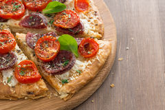 Delicious pizza with salami and tomatoes on a wooden background. Top view, close-up royalty free stock images