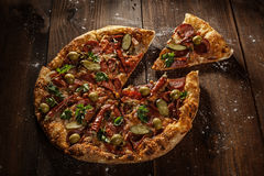 Delicious pizza with slice served on wooden table royalty free stock photography