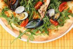 Delicious pizza on wooden plate Royalty Free Stock Images
