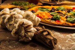 Pizza and Garlic. A delicious pizza on a wooden table served on a plate with garlic in foreground royalty free stock photos
