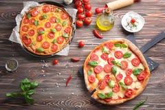 Delicious pizzas on kitchen. Table Stock Photos