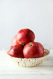 Delicious pomegranate fruit in basket on the white wooden background Royalty Free Stock Image