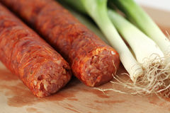 Delicious pork sausage with onion on wooden plate Royalty Free Stock Photos