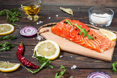 Delicious portion of fresh salmon fillet with aromatic herbs, spices and vegetables - healthy food, diet or cooking concept. Stock Images