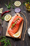 Delicious portion of fresh salmon fillet with aromatic herbs, spices and vegetables - healthy food, diet or cooking concept. Stock Photo