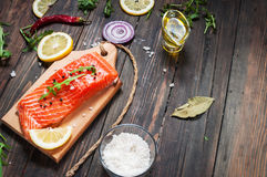 Delicious portion of fresh salmon fillet with aromatic herbs, spices and vegetables - healthy food, diet or cooking concept. Stock Photos