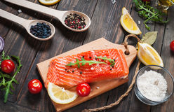 Delicious portion of fresh salmon fillet with aromatic herbs, spices and vegetables - healthy food, diet or cooking concept Royalty Free Stock Photography