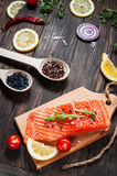 Delicious portion of fresh salmon fillet with aromatic herbs, spices and vegetables - healthy food, diet or cooking concept Royalty Free Stock Photo