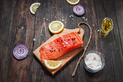 Delicious portion of fresh salmon fillet with aromatic herbs, spices and vegetables - healthy food, diet or cooking concept. Flat lay Stock Image