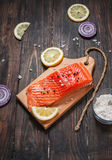 Delicious portion of fresh salmon fillet with aromatic herbs, spices and vegetables - healthy food, diet or cooking concept. Flat lay Stock Images
