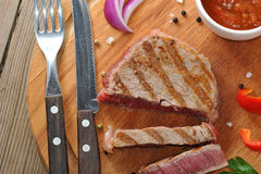 Delicious portion of healthy grilled lean medium rare beef steak. Cut through and served on a wooden kitchen board Royalty Free Stock Image
