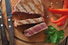 Delicious portion of healthy grilled lean medium rare beef steak. Cut through and served on a wooden kitchen board Royalty Free Stock Photography