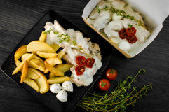 Delicious portion of rustic potatoes fillet with aromatic herbs Royalty Free Stock Photo