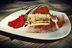 Delicious portion of tiramisu on white saucer Stock Photography