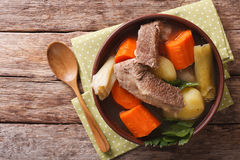 Delicious Pot-au-feu beef soup with vegetables close up in a bow. L on the table. horizontal view from above Royalty Free Stock Images