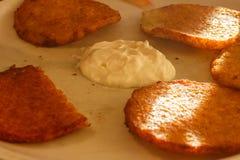 Delicious potato pancakes on plate with sour cream Royalty Free Stock Photos