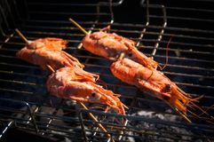 delicious prawn spit on grill with flames in background stock image
