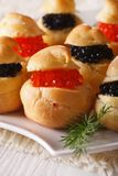 Delicious profiteroles with red and black caviar, vertical Stock Image