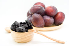 Delicious prunes in wooden bowl and fresh plums Stock Image