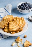 Delicious puff pastry cookies, and blueberries on delicate blue background royalty free stock image
