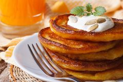 Delicious pumpkin pancakes with sour cream and juice macro Royalty Free Stock Photo