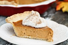 Delicious Pumpkin Pie Slice with Whiiped Cream. Slice of homemade pumpkin pie with topping and sprinkled with pumpkin pie spice. Extreme shallow depth of field royalty free stock photography