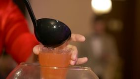 Delicious punch at party. Bartender at the ceremony pours with the scoop sweet tasty fragrant apple punch in glass stock footage