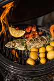 Delicious rainbow trout fish with tomatoes, potatoes and lemon cooking on hot flaming grill. Barbecue. Restaurant stock photography