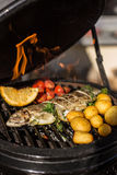 Delicious rainbow trout fish with tomatoes, potatoes and lemon cooking on hot flaming grill. Barbecue. Restaurant stock images